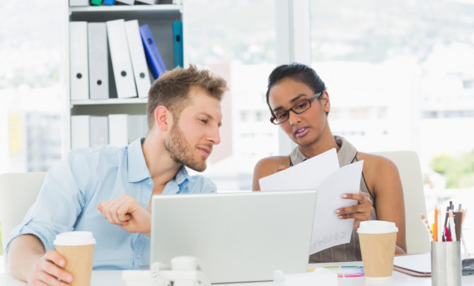 Partners working together on laptop at desk