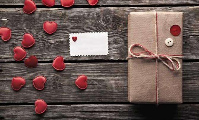 Vintage gift box with small hearts on wooden table.