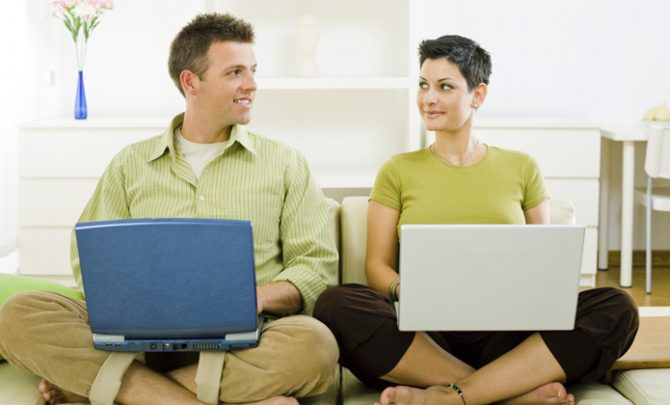 Young couple sitting on a sofa cross-legged in the living room, using laptops, looking at each other. [url=my_lightbox_contents.php?lightboxID=1507925][img]http://www.nitorphoto.com/istocklightbox/peopleathome.jpg[/img][/url]